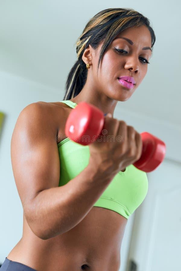 La femme de couleur la maison de forme physique forme le biceps avec des poids image stock - La maison des couleurs ...