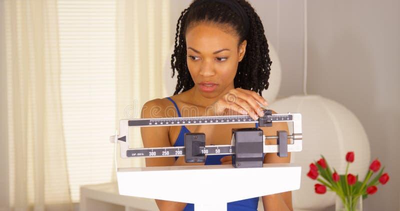 La femme de couleur déçue vérifie le poids photos stock