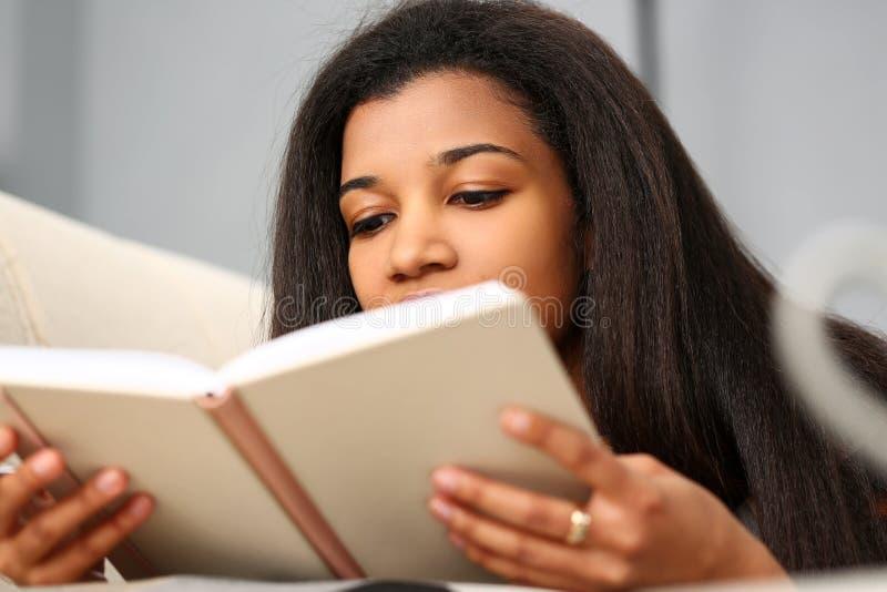 La femme de couleur de sourire a lu le livre d'histoire ? la maison photographie stock