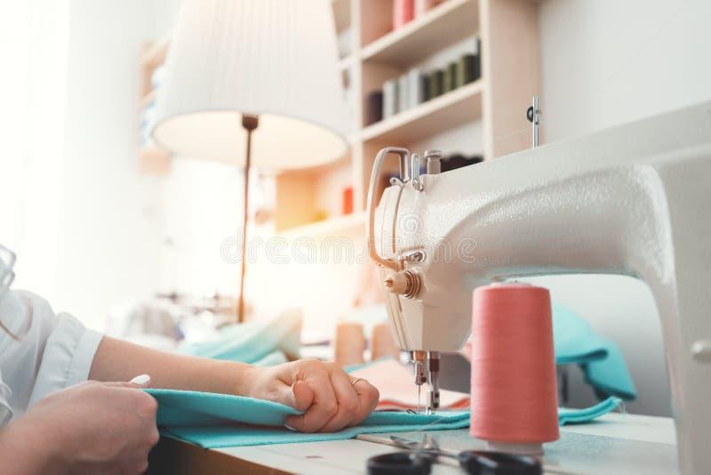 La femme de couturière coud des vêtements sur la machine à coudre dans le bureau de conception L'ouvrière couturière et ses mains images stock