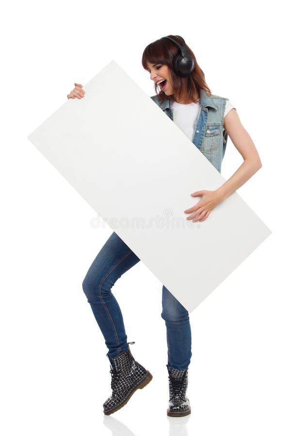 La femme de cri tient la bannière blanche et feint jouant la guitare photos stock