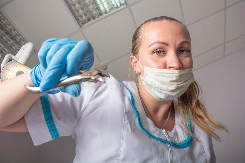 La femme de docteur dans un masque médical et avec le forceps dans des ses mains enlève une dent, plan rapproché image stock