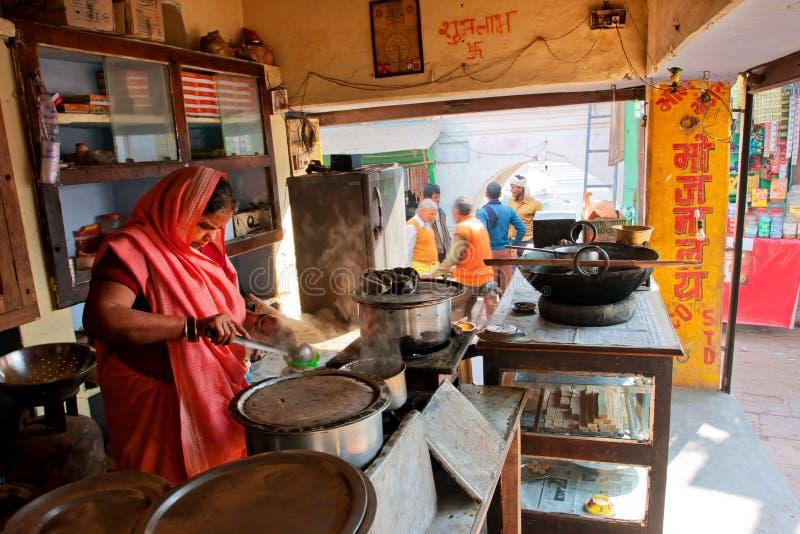 La femme de femme fait cuire la nourriture dans un café extérieur sur la rue indienne serrée image libre de droits