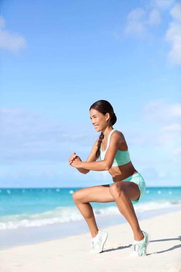 La femme de forme physique faisant des veaux de formation de séance d'entraînement de poids du corps avec le plie s'accroupissent image libre de droits