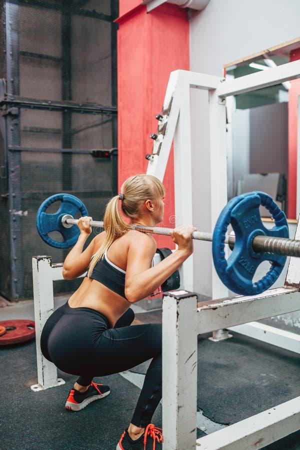 La femme de forme physique faisant le barbell s'accroupit dans un gymnase images stock
