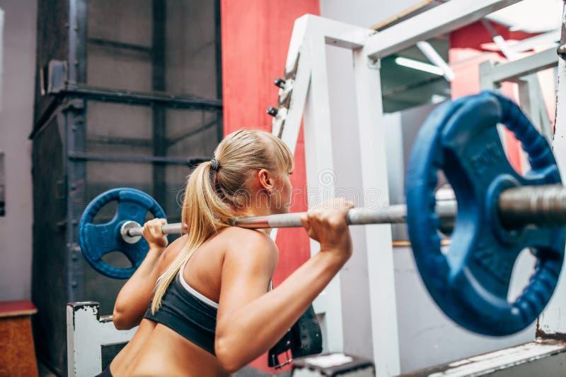 La femme de forme physique faisant le barbell s'accroupit dans un gymnase photographie stock