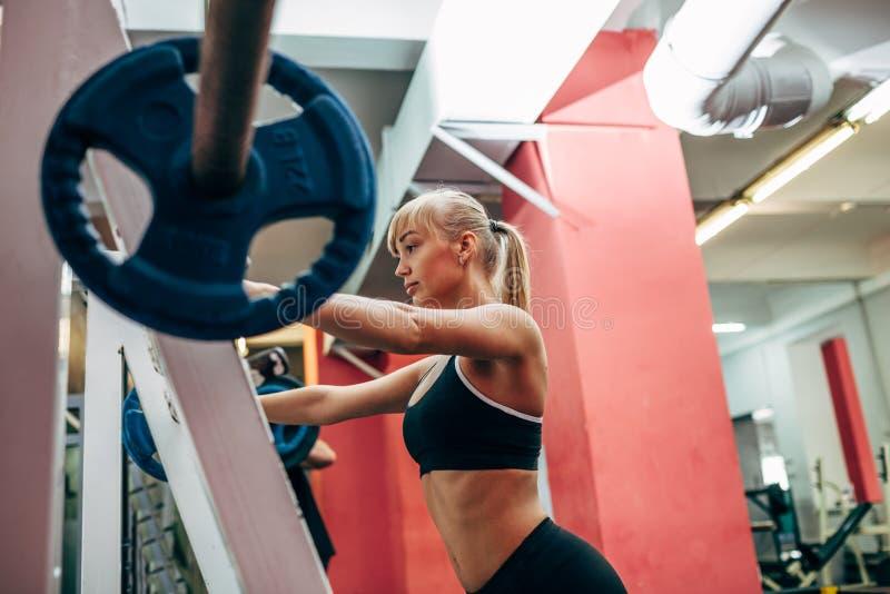 La femme de forme physique faisant le barbell s'accroupit dans un gymnase photos stock