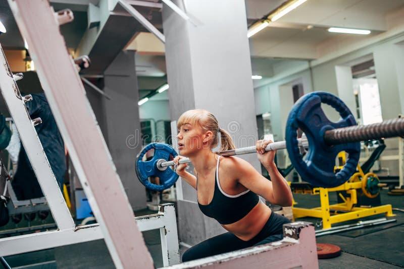 La femme de forme physique faisant le barbell s'accroupit dans un gymnase photo libre de droits
