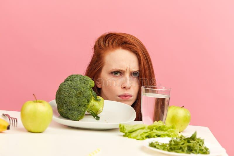 La femme de froncement de sourcils déteste des légumes sur la table avec la grimace répugnante d'isolement images libres de droits