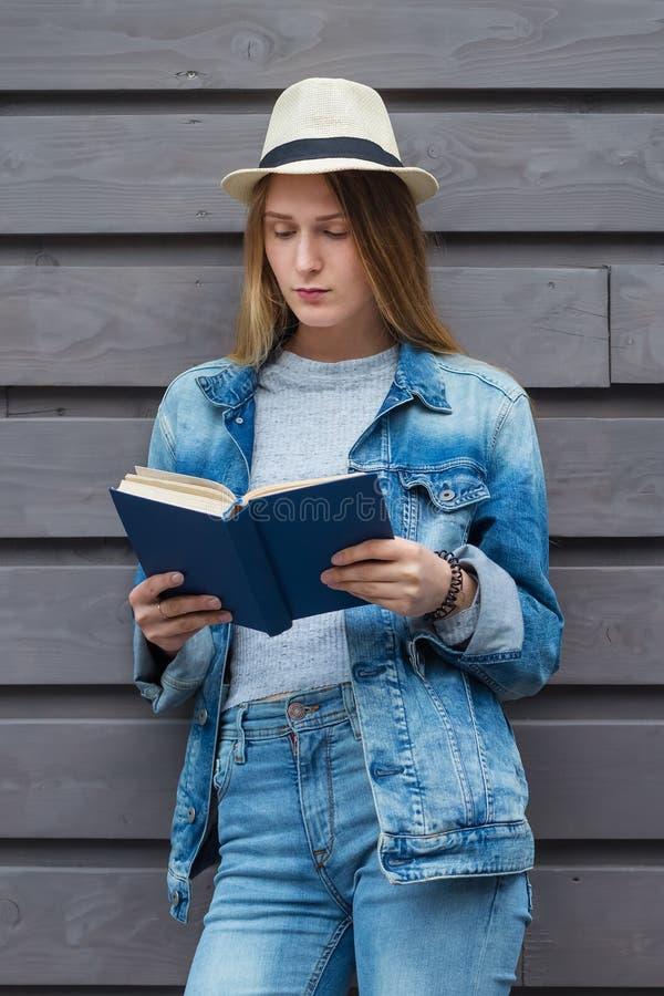 La femme de l'adolescence a lu le livre en dehors du mur image stock