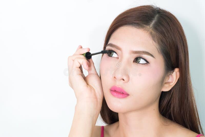La femme de maquillage mettant l'oeil de mascara composent sur des yeux Fa frais asiatique photos stock
