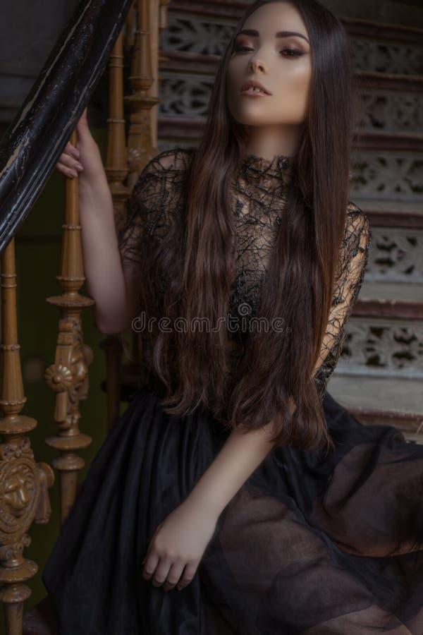 La femme de mode de beauté avec de longs cheveux et smokey observe, se reposant sur la robe élégante de port de concepteur de cai images stock