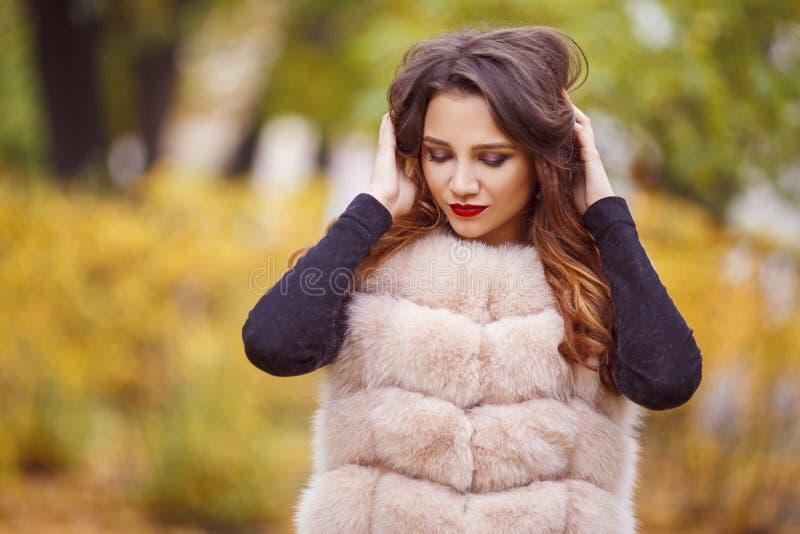 La femme de mode de beauté dans le gilet de fourrure marche en parc Automne photographie stock