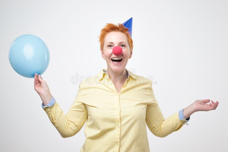 La femme de mode envoie un baiser d'air avec les ballons colorés sur le fond bleu photo stock