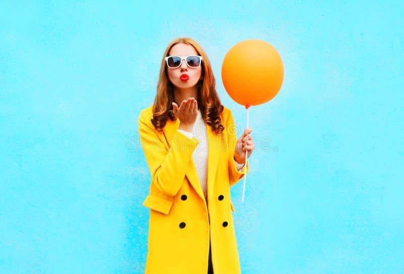 La femme de mode envoie un ballon de prises de baiser d'air dans un manteau jaune image stock
