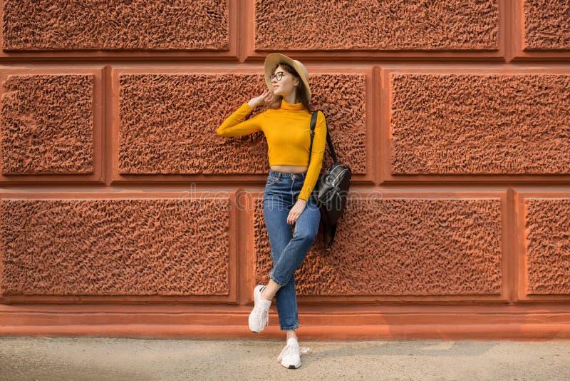 La femme de mode se tient près du mur orange photographie stock libre de droits