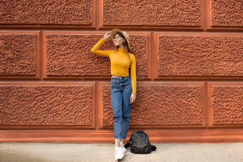 La femme de mode se tient près du mur orange photos libres de droits