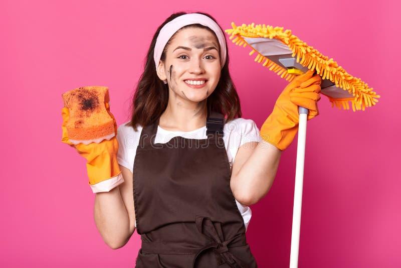 La femme de nettoyage européenne gaie se lève ses mains avec l'équipement de lavage, finit ses travaux domestiques, semble heureu photo libre de droits