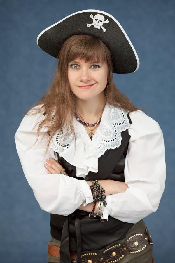La femme de pirate pose avec émotion sur le fond bleu photos stock