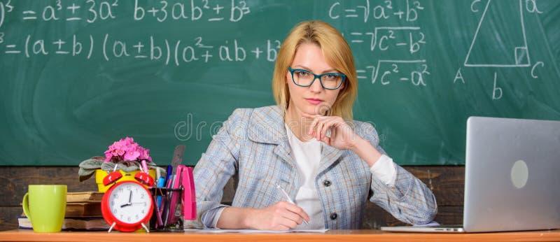 La femme de professeur reposent le fond de tableau de salle de classe de table Leçon actuelle de la façon complète pour faciliter photos libres de droits