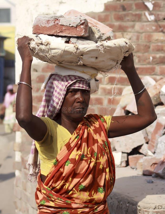 La femme de Roma porte des briques sur sa tête images libres de droits