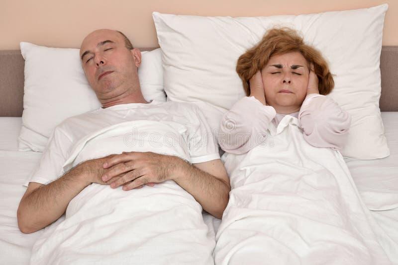 La femme de ronflement de moment d'homme ne peut pas dormir photographie stock libre de droits