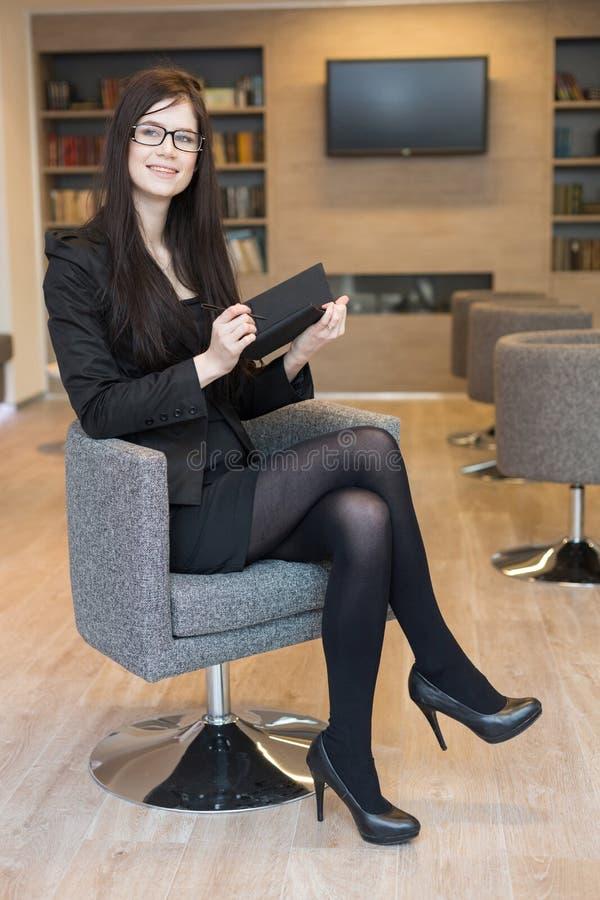 La femme de sourire d'affaires en verres s'assied sur une chaise images stock