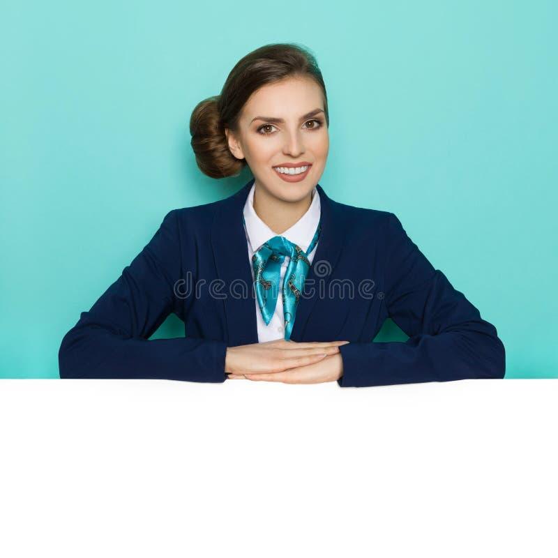 La femme de sourire dans le costume bleu juge des bras croisés sur la bannière blanche photo stock