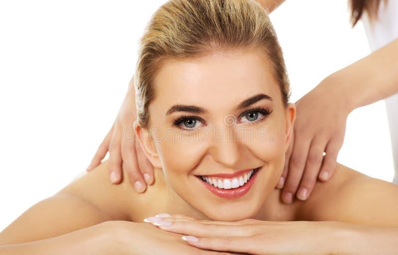 La femme de sourire de jeunes se trouvant sur une table de massage et a le massage photographie stock libre de droits