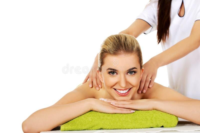 La femme de sourire de jeunes se trouvant sur une table de massage et a le massage photo libre de droits