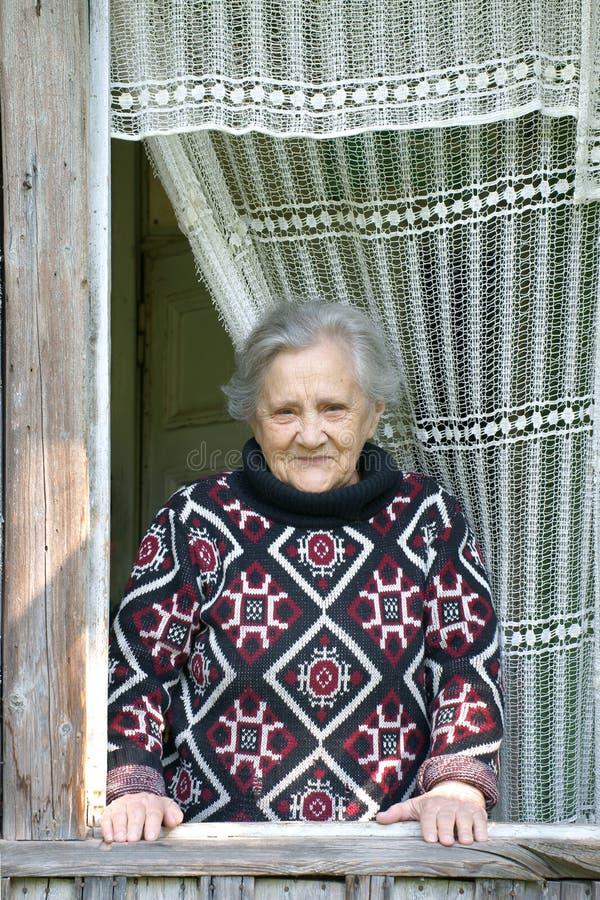 La femme de sourire de personnes âgées regarde à l'extérieur l'hublot ouvert de photos stock