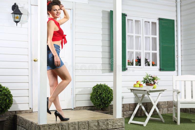 La femme de sourire en bref se tient à côté de la porte d'entrée blanche images libres de droits