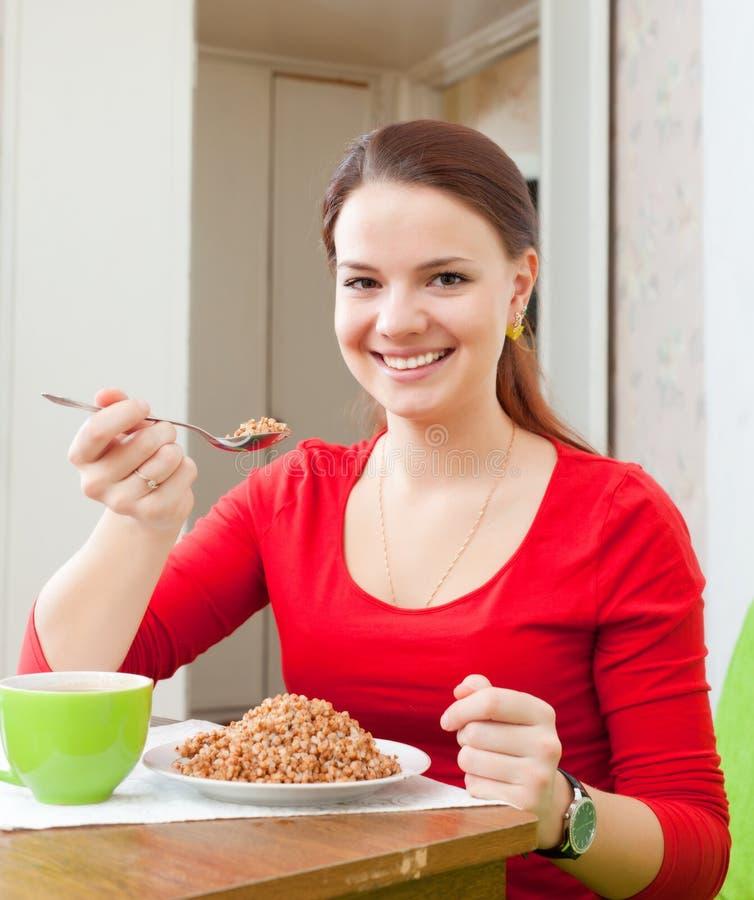 La femme de sourire en rouge mange du sarrasin photos stock