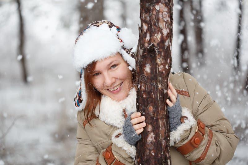 La femme de sourire heureuse dans le manteau avec la fourrure blanche, chapeau avec l'oreille agite a images stock