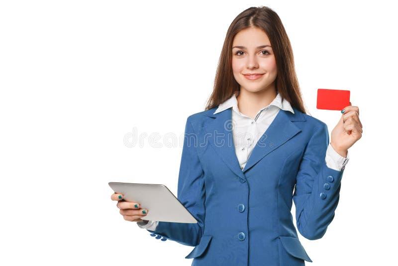 La femme de sourire montrant la carte de crédit en blanc jugent le PC de comprimé disponible, d'isolement au-dessus du fond blanc image stock