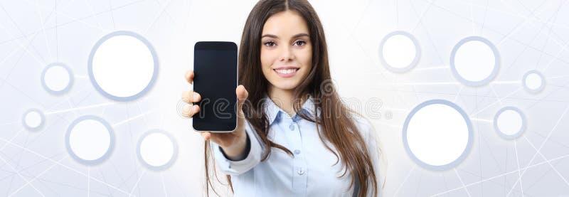 La femme de sourire montre le smartphone, media social, réseau social photographie stock
