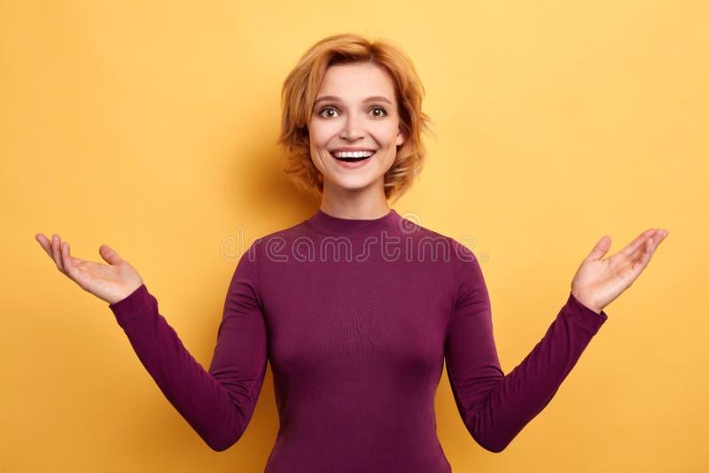 La femme de sourire satisfaite soulève des mains et des regards à la caméra images stock