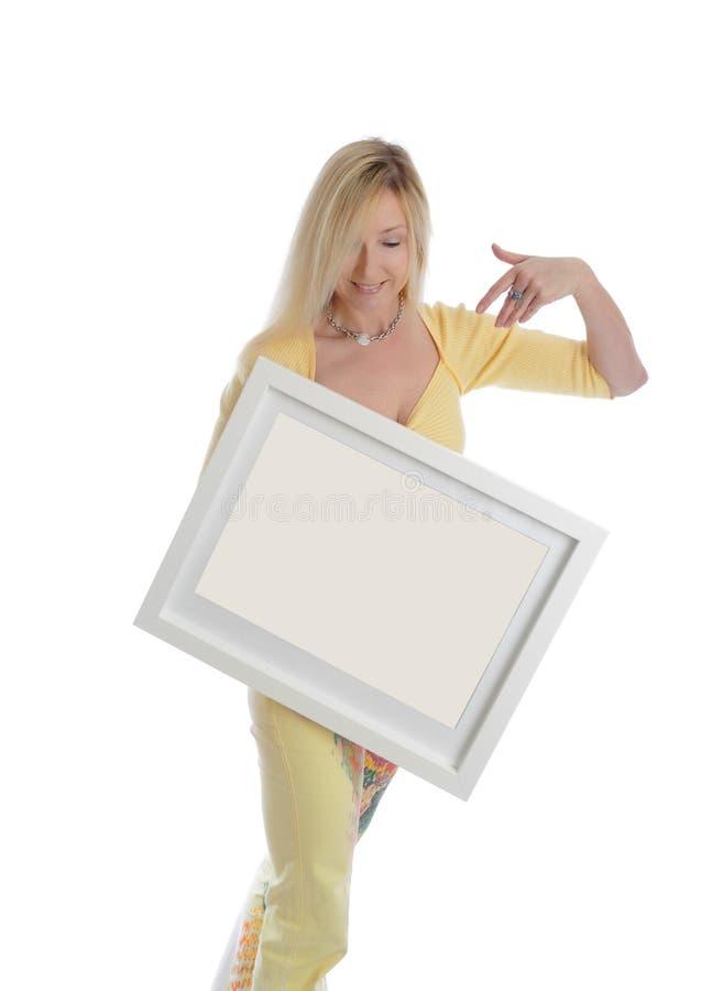 La femme de sourire tenant une peinture de photo signent le message photo libre de droits