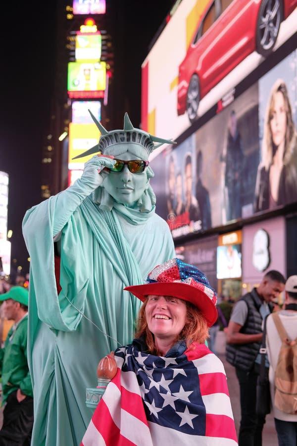 La femme de sourire vue a drapé dans un drapeau des USA et le chapeau des USA photographie stock libre de droits