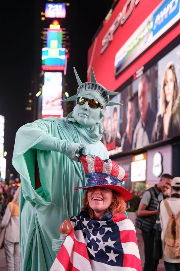 La femme de sourire vue a drapé dans un drapeau des USA et le chapeau des USA images libres de droits