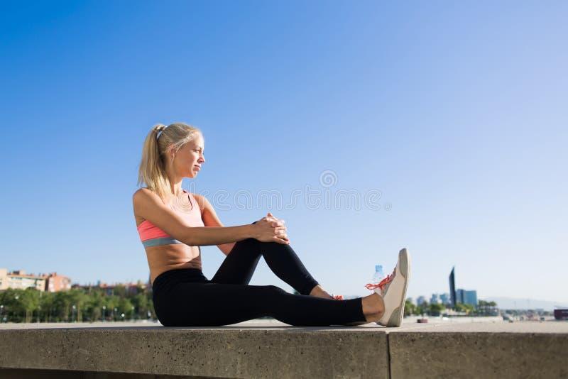 La femme de sports de jeunes a plaisir à se reposer après séance d'entraînement dehors images stock