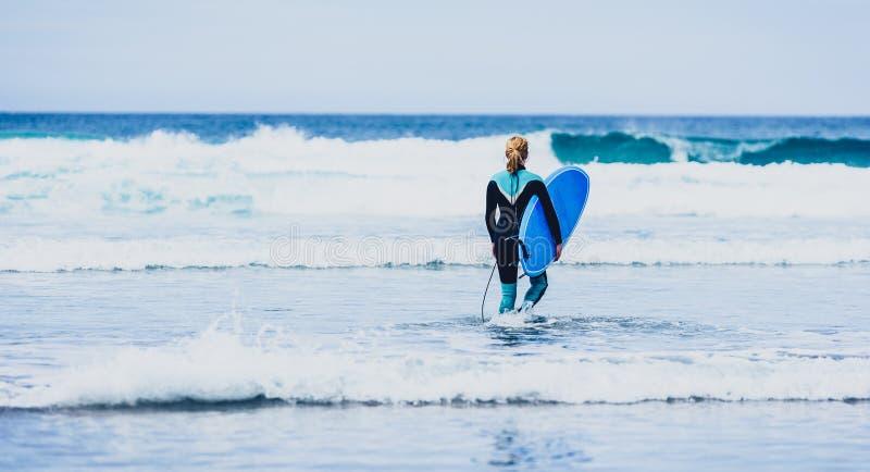 La femme de surfer avec la planche de surf est marchante et observante les vagues photo libre de droits