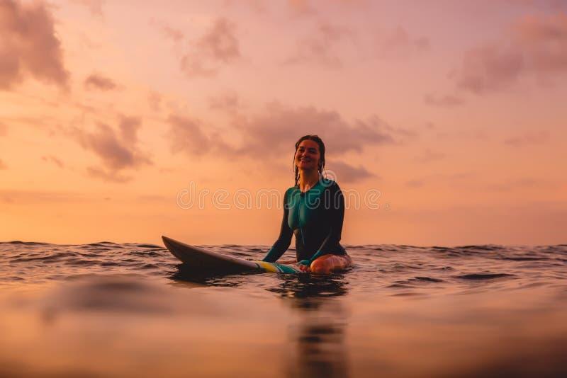 La femme de surfer s'asseyent sur une planche de surf dans l'oc?an photo libre de droits