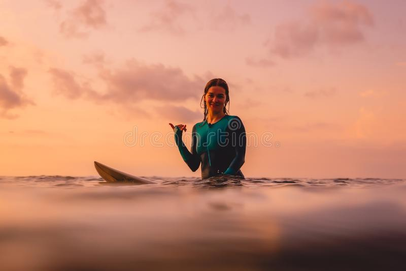 La femme de surfer s'asseyent sur une planche de surf dans l'oc?an Surfer au coucher du soleil image libre de droits