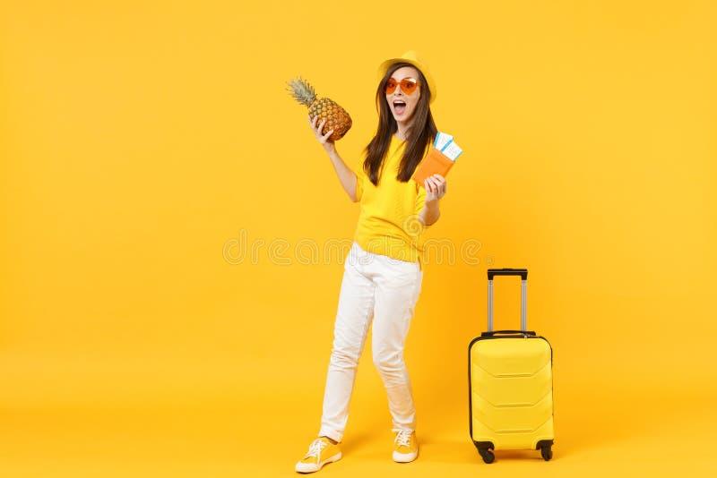 La femme de touristes étonnée de voyageur dans le passeport de participation de chapeau étiquette le fruit frais d'ananas d'isole photo libre de droits