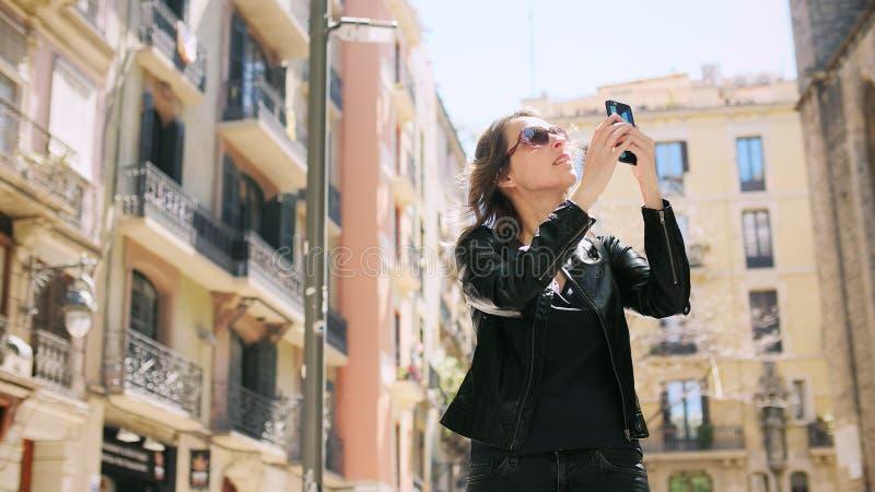 La femme de touristes attirante faisant un selfie emploie un smartfone tout en marchant à la rue image libre de droits