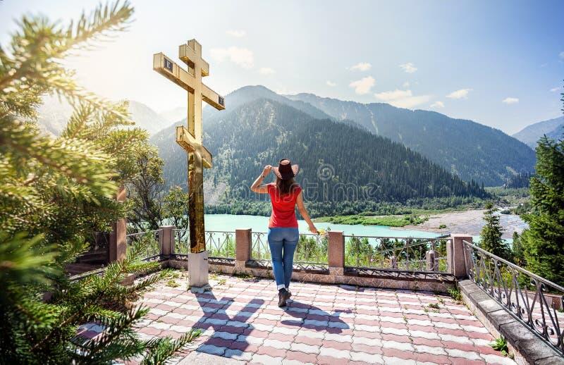 La femme de touristes aux montagnes s'approchent de la croix d'or photo stock