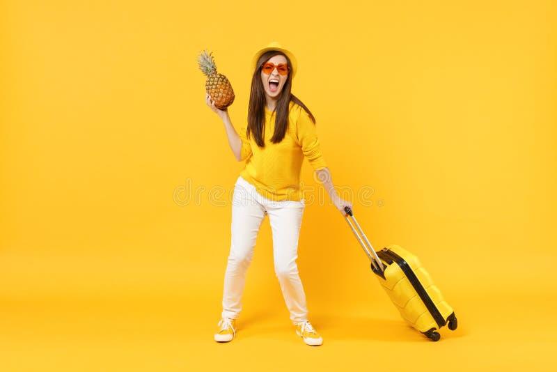 La femme de touristes criarde de voyageur dans le chapeau de vêtements d'été jugent le fruit mûr frais d'ananas d'isolement sur j photographie stock libre de droits