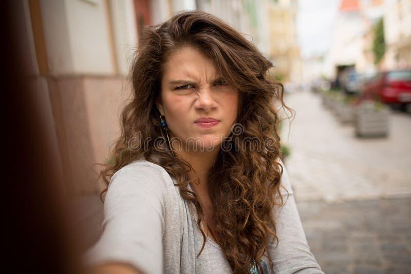 La femme de touristes dans la rue sur le selfie a tiré montrer le visage sombre image libre de droits