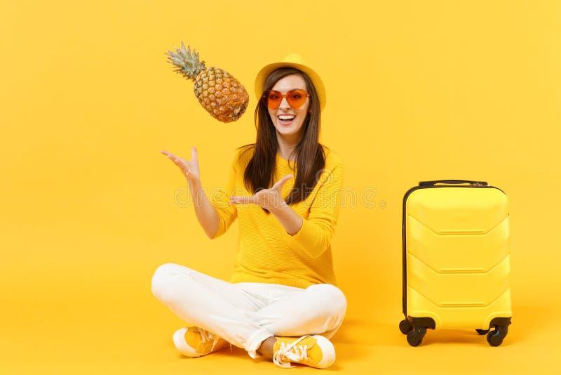 La femme de touristes de voyageur gai dans des vêtements d'été, chapeau jettent vers le haut du fruit frais d'ananas d'isolement  photos stock